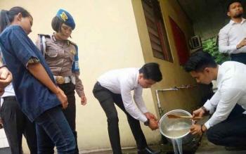 Anggota Satreskoba Polres Kotim membuang sabu yang dilarutkan dalam air, ke selekon, saat pemusnahan barang bukti, di Sampit, Senin (28/11/2016). BORNEONEWS/M. HAMIM
