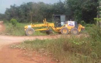 Sebuah alat berat jenis grader bergambar pasangan nomor 4 (Sidin) sedang bekerja membersihkan jalan di sebuah desa. BORNEONEWS/DOK