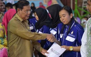 Sekda Barito Utara, H Jainal Abidin saat menyerahkan beasiswa kepada siswa SMKN 1 Muara Teweh pada kegiatan peringatan HUT SMKN 1 Muara Teweh, Selasa (29/11/2016). BORNEONEWS/RAMADANI