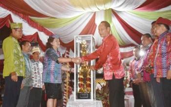 Bupati Gunung Mas Arton S Dohong menyerahkan piala bergilir Gubernur Kalteng kepada pimpinan kontingen Kota Palangka Raya atas prestasi meraih juara umum pada kegiatan Festival Tandak Intan Kaharingan (FTIK) ke VIII, Selasa (29/11/2016). BORNEONEWS/EPRA S