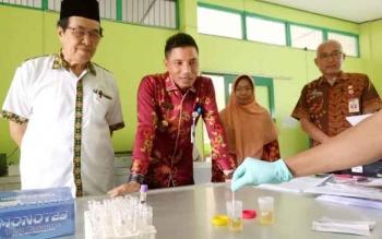 Bupati dan wakil Bupati Kotim Supian Hadi-M Taufiq Mukir memperhatikan proses tes urine mereka yang dilakukan di laboratorium Kesehatan Daerah (Labkesda) Kotim, Kamis (1/12/2016). BORNEONEWS/RAFIUDIN