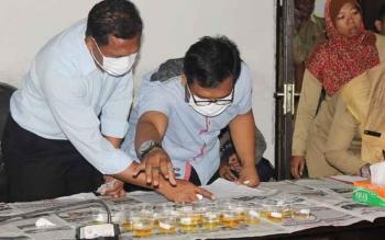 Petugas Satreskoba Polres Kotim memeriksa urin pegawai Setda Kotim saat tes urin serentak pegawai di instansi itu beberapa waktu lalu. BORNEONEWS/RAFIUDIN
