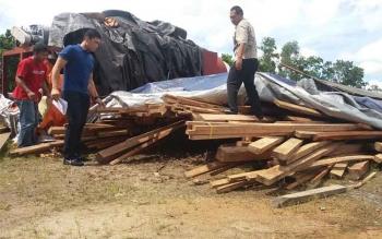 Kasat Reskrim Polres Kotim Iptu Reza Fahmi bersama dua anggotanya sedang melakukan pemeriksaan terhadap kayu yang ditahan mereka, Minggu (4/12/2016). BORNEONEWS/HAMIM/m