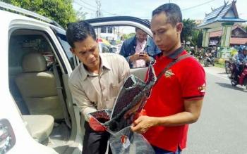 Kanit Reskrim (kiri) Ipda Jaka Waluya dan anggotanya memasukan barang bukti pecahan kaca mobil, Selasa (6/12/2016) BORNEONEWS/BUDI YULIANTO