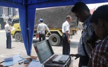 Petugas Dinas Perhubungan Komunikasi dan Informatika Kabupaten Kotawaringin Timur saat mengukur kendarean yang beroperasi di daerah itu. BORNEONEWS/HAMIM