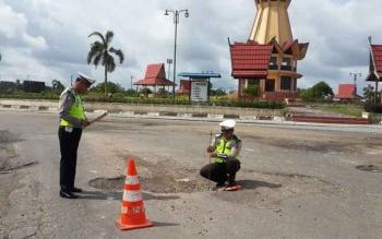 Dua anggota Unit Dikyasa Satlantas Polres Kobar, Kamis (8/12/2016), tengah mengukur kerusakan jalan di depan pos jaga Satlantas di Bundaran Simpang Lima (Pangkalan Lima) Jalan Ahmad Yani, Pangkalan Bun. BORNEONEWS/CECEP HERDI