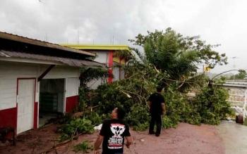 Tampak pemilik kios BBM di jalan Ahmad Yani, Ahan (kaos hitam) dibantu sejumlah warga sekitar saat membersihkan puing-puing dahan pohon yang roboh akibat hujan deras yang disertai angin ribut, Kamis (8/12/2016) siang.