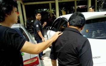 Kepala Seksi Pelaporan Disdukcapil Palangka Raya, Ru (depan) digiring polisi menuju mobil, untuk kemudian dibawa ke kantor Ditreskrimum Polda Kalteng, Kamis (8/12/2016). BORNEONEWS/BUDI YULIANTO