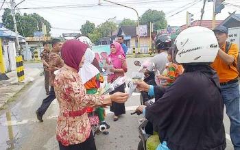 Di perempatan jalan dan lampu merah di Kota Buntok, Jumat (9/12/2016), sejumlah Jaksa membagikan bunga dan stiker anti korupsi kepada masyarakat dalam rangka hari anti korupsi sedunia. BORNEONEWS/PPOST/H. LAILY MANSYUR