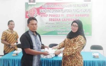 Ketua PWI Seruyan, M Yadi menerima brosur tentang peran serta masyarakat dalam pemberantasan tindak pidana korupsi dari Kepala Kejaksaan Negeri Seruyan, Jasmaniar, Jumat (9/12/2016). BORNEONEWS/PARNEN