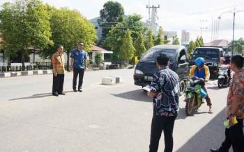 Pegawai Kejaksaan Negeri Barito Utara membagikan pin dan stiker kepada masyarakat di jalan Yetro Sinseng, di depan kantor kejaksan negeri, Jumat (9/12/2016). BORNEONEWS/RAMADANI