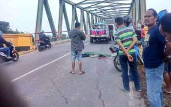 Jasad kakek Bustani (60), tertutup daun pisang, tergeletak di atas Jembatan Pulau Petak, Jumat (9/12/2016). BORNEONEWS/PPOST/SRI HAYATI