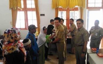 Bupati Barito Utara, H Nadalsyah didampingi Wakil Bupati Ompie Herby menyerahkan bantuan kepada masyarakat kurang mampu, di kantor Dinsosnakertrans Barut, di Muara Teweh, Selasa (27/12/2016). BORNEONEWS/RAMADANI