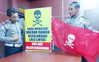 Kasat Lantas Polres Palangka Raya AKP Christian Maruli Tua Siregar (kiri) dan Kanit Laka Aiptu Tri Marsono menunjukan banner tengkorak, Rabu (28/12/2016).