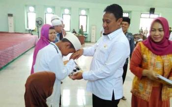Bupati Pulang Pisau menyerahkan bantuan buku kepada peserta festival anak sholeh.