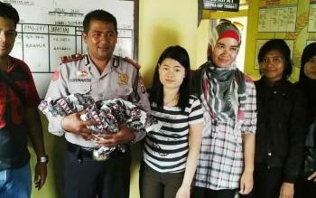 Kapolsek Kahayan Hilir Iptu Sugiharso menggendong bayi perempuan yang ditemukan warga Buntoi di teras rumah, Sabtu (31/12/2016).