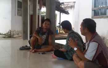 Kumau, adik kandung Buandi, bersama anggota keluarga lainnya menunggu jenazah sang kakak di Rumah Sakit Jaraga Sasameh Buntok, Kabupaten Barito Selatan, Minggu (1/1/2017).