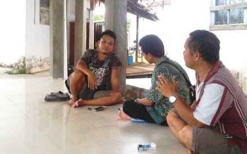 Adik kandung Buandi, Kumau (kiri) bersama anggota keluarga lainnya menunggu hasil visum sang kakak di Rumah Sakit Jaraga Sasameh Buntok. (BORNEO/URIUTU/DOK)