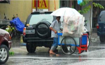 Seorang penjual jajanan nampak menutupi dagangannya dengan plastik saat terjadinya hujan yang sering turun secara tiba-tiba belakangan ini. BORNEONEWS/WAHYU KRIDA