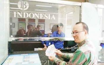 Plt Kepala Perwakilan Bank Indonesia Kalimantan Tengah, Setian,menukarkan uang rupiah lamanya dengan uang rupiah baru. Di Kobar, uang pecahan baru ini masih sulit didapat.BORNEONEWS/DOK