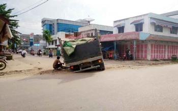 Sebuah truk bermuatan semen amblas di bekas galian pipa PDAM. BORNEONEWS/HAMIM