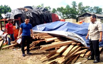 Kasat Reskrim Polres Kotim AKP Reza Fahmi bersama sejumlah anggotanya sedang memeriksa kayu ilegal yang diamankan, beberapa waktu lalu. BORNEONEWS/HAMIM