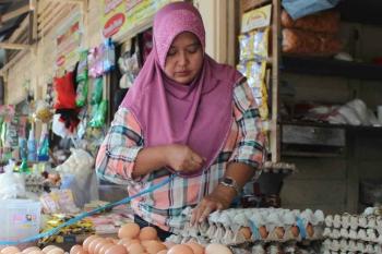 Seorang pedagang sembako di Kuala Pembuang di sela-sela kesibukannya menunggu pembeli datang, Minggu (8/1/2017). (BORNEONEWS/PARNEN)