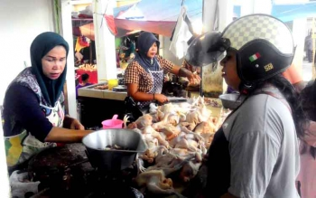 Pedagang ayam potong di Pasar Blok R, Kuala Kapuas, Kabupaten Kapuas, Siti Arbaina melayani pembeli, Minggu (8/1/2017). (BORNEONEWS/DJIMMY NAPOLEON)