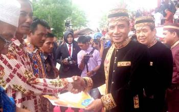 Bupati Kotim Supian Hadi didampingi Wakil Bupati M Taufiq Mukri menyerahkan asuransi kepada nelayan di daerah itu usai upacara HUT Kotim, Sabtu (7/1/2017) lalu.(BORNEONEWS/RAFIUDIN)
