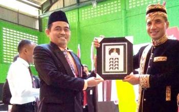 Kepala Kantor Pos Sampit Muhdi menyerahkan prangko Prisma kepada Bupati Kotim Supian Hadi. (BORNEONEWS/M.HAMIM)