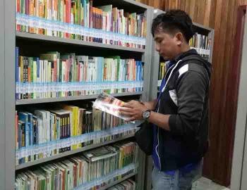 Seorang pengunjung memilih buku di perpustakaan DKP Sukamara. BORNEONEWS/NORHASANAH