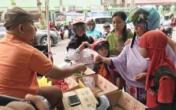 Kasi Pelayanan Publik Bulog Subdivre Sampit M Azwar Fuad, melayani warga yang membeli cabai dalam operasi pasar cabai yang digelar Bulog Subdivre Sampit, di sekitar Mesjid Baiturrahim Sampit, Jumat (23/1/2017). BORNEONEWS/M RIFQI