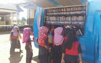 Anak-anak Desa Bukit Sungkai Kecamatan Balai Riam Kabupaten Sukamara saat memilih buku di perpustakaan keliling. BORNEONEWS/NORHASANAH