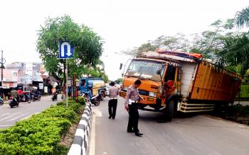 Sejumlah polisi lalu lintas sedang memeriksa kondisi truk yang amblas di Jl Sampurna-Jl Tjilik Riwut, Jumat (13/1/2017).