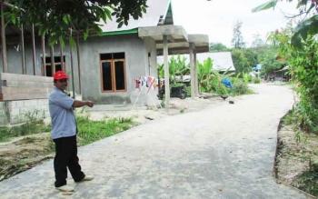Kepala Desa Petak Bahandang Gad Ihing memperlihatkan jalan desa yang telah dibangun pada 2016 dengan dana desa dan ADD. BORNEO/EPRA SENTOSA