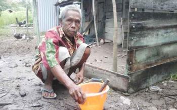 Kakek Saribi (60) saat memperbaiki rumahnya bagian belakang. BORNEONEWS/PARNEN