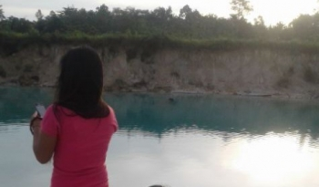 BERSANTAI : Seorang perempuan sedang bersantai di danau biru. Di danau inilah Stevan Daniel tewas tenggelam. BORNEONEWS/SUPRI ADI