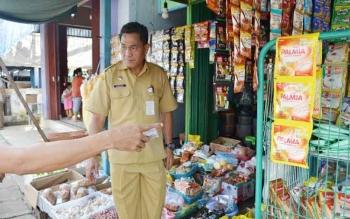 Kepala Disperindagkop Mura, Kariadi saat meninjau harga bahan pokok di Kota Puruk Cahu. BORNEONEWS/SUPRI ADI