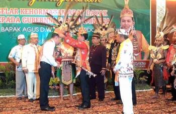 Ketua DAD Kalteng Agustiar mengenakan topi khas Dayak kepada Gubernur BI Agus Martowardojo. BORNEONEWS/TESTI PRISCILLA