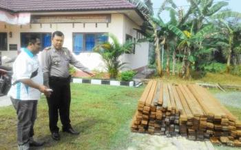 Kapolsek Dusun Selatan, AKP Budiono, Selasa (17/1/2017), menunjukkan kayu hasil Illegal Logging yang diamankan petugas dari dua tersangka, Kudran alias Udet (47) dan Muhammad Tamsil (35), Minggu (15/1/2017). BORNEONEWS/PPOST/H. LAILY MANSYUR