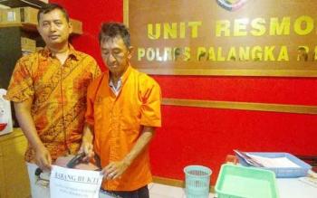 Kasat Reskrim Polres Palangka Raya AKP Ismanto Yuwono (kiri) menunjukan pencuri chainsaw dan barang buktinya, Selasa (17/1/2017). (BORNEONEWS/BUDI YULIANTO)