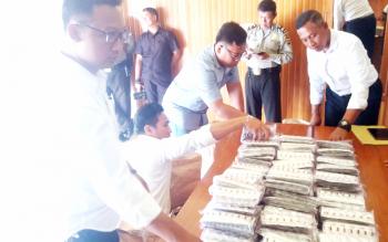 Anggota Satreskoba Polres Kotim merapikan barang bukti zenith yang diamankan dari salah seorang tersangka pengedar perempuan. BORNEONEWS/HAMIM