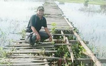 Anggota DPRD Barito Selatan, Anwar Supiansyah saat melakukan kunjungan kerja dan melihat jembatan titian Pakat Pahari rusak parah. BORNEONEWS/URIUTU DJAPER