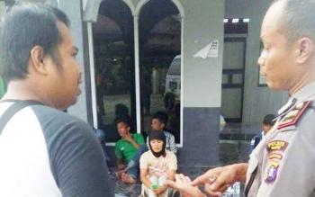 Kartini, adik korban Kamani, terduduk sambil meneteskan air mata di dekat kamar jenazah RSUD Muara Teweh, Kabupaten Barito Utara, Kamis (19/12017). (BORNEO/RAMADHANI)