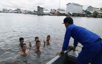 Personel Ditpolair Polda Kalteng di Kuala Jelai, Brigadir Yudi Supiandi saat memperingatkan anak-anak yang berenang di sungai. BORNEONEWS/NORHASANAH