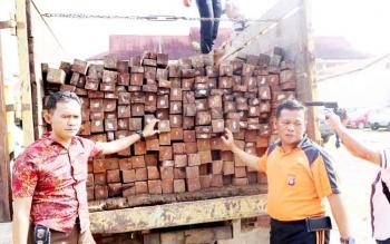 Kabid Humas Polda Kalteng AKBP Pambudi Rahayu (kanan) menunjukan barang bukti kayu olahan campuran jenis ulin dan benuas yang diamankan polisi, Jumat (20/1/2017). (BORNEO/BUDI YULIANTO)