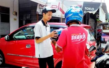 OJEK ONLINE-Normansyah saat menyerahkan helm kepada pelanggan yang menggunakan layanannya. Keamanan menjadi prioritas dalam berkendara. BORNEONEWS/TESTI PRISCILLA