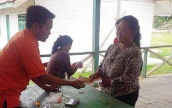 Petugas Kantor Pos Nanga Bulik, menyalurkan dana PKH di Desa Merambang, Bulik Timur, beberapa waktu lalu. Dinsos Lamandau pastikan jumlah penerima bantuan PKH dari Kementerian Sosial 2016, ada tambahan 171 sasaran. BORNEONEWS/HENDI NURFALAH