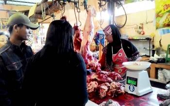 DAGING SAPI - Seorang penjual daging sapi di Pasar Kahayan Palangka Raya tengah melayani pembeli di lapaknya, Senin (23/1/2017). BORNEONEWS/TESTI PRISCILLA
