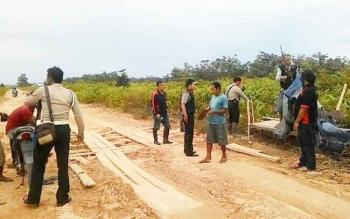 Anggota Polsek Kotawaringin Lama membongkar sejumlah portal di Jalan Pangkalan Bun-Kotawaringin Lama. (BORNEONEWS/FAHRUDDIN FITRYA)